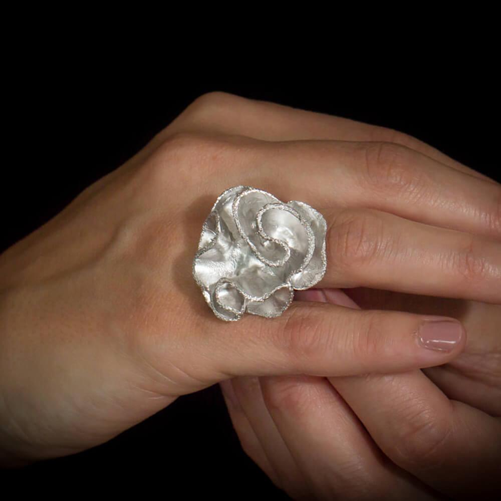 Zilveren bloemring, krulvormig en gediamanteerd