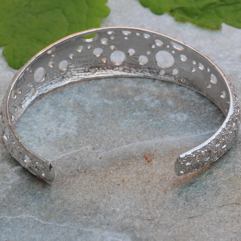 Smalle en zilveren armband met bewerkte schitteringen