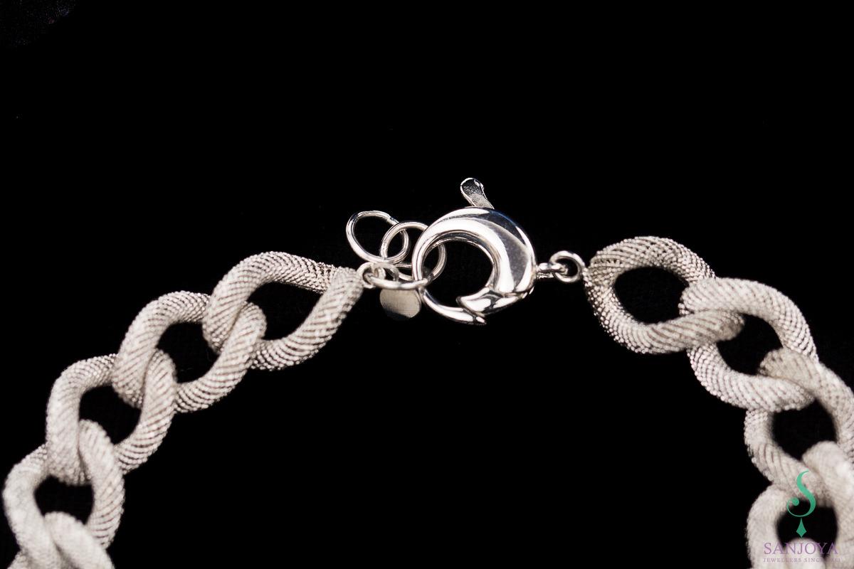 Smalle zilveren schakelarmband met transparant patroon