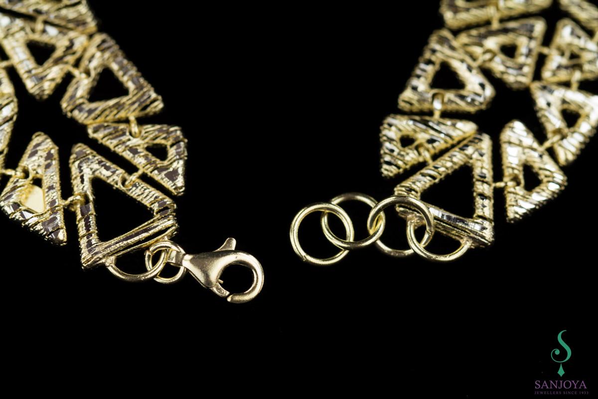 Bewerkte armband met vergulde driehoekjes