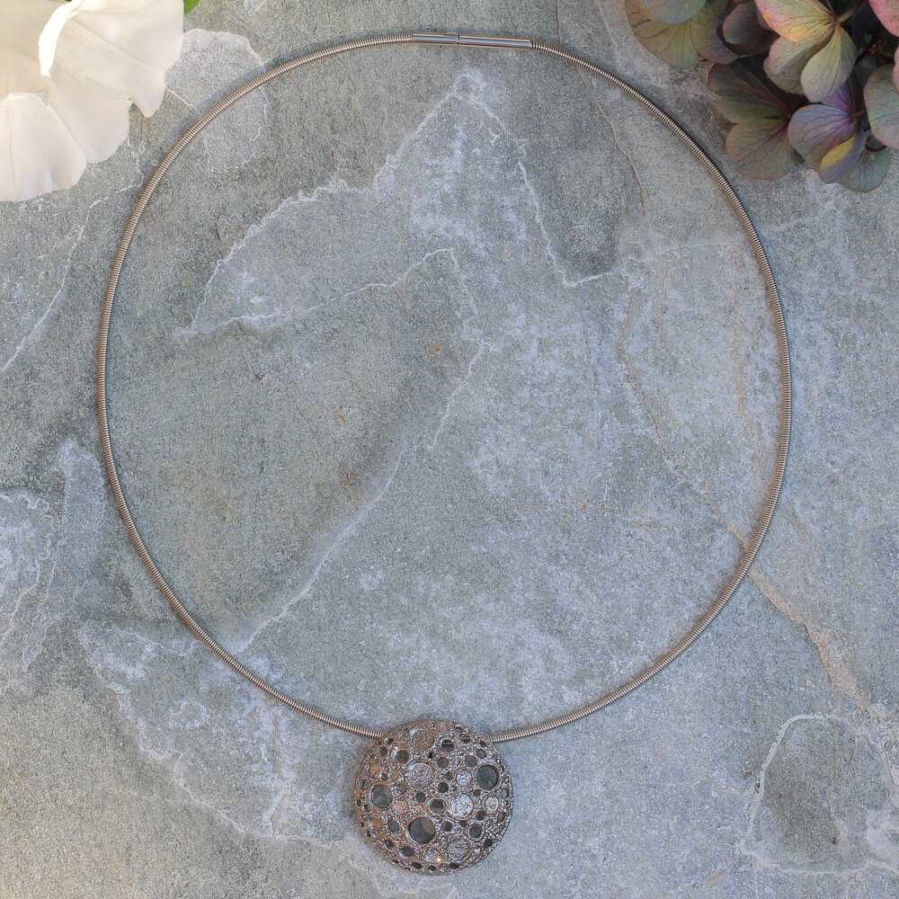 Grijze hanger met onregelmatige schitterende gaatjes